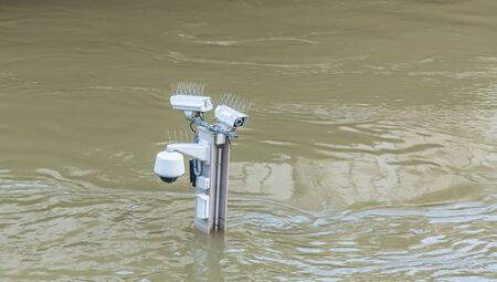scourge: Paris,France - June 05, 2016: Surveillance cameras on the top of a pole are almost covered by water on the River Seine embankment after the massive flooding in Paris during the first days of June 2016. Stock Photo