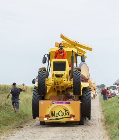 mc: Quievy,France - July 07, 2015:  Mc Cain Caravan during the passing of the Publicity Caravan on a cobblestoned road in the stage 4 of Le Tour de France on July 7 2015 in Quievy, France. Mc Cain is a market leader in frozen products made from potatoes.