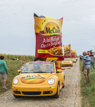 publicity: Quievy,France - July 07, 2015:  Mc Cain Caravan during the passing of the Publicity Caravan on a cobblestoned road in the stage 4 of Le Tour de France on July 7 2015 in Quievy, France. Mc Cain is a market leader in frozen products made from potatoes.