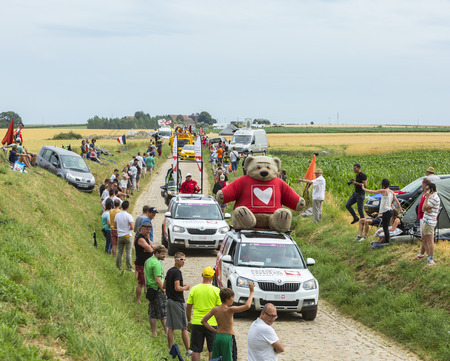 cardiac surgery: Quievy,France - July 07, 2015: The association Cardiac Surgery - Children of the World Caravan during the passing of the Publicity Caravan on a cobblestoned road in the stage 4 of Le Tour de France on July 7 2015 in Quievy, France. The association Cardiac