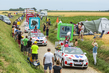 carrefour: Quievy,France - July 07, 2015: Carrefour Caravan during the passing of the Publicity Caravan on a cobblestoned road in the stage 4 of Le Tour de France on July 7 2015 in Quievy, France.