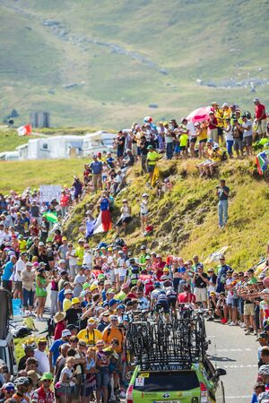 bono: Col du Glandon, France - July 23, 2015: Group of cyclists followed by a technical car, riding on the road to Col du Glandon in Alps during the stage 18 of Le Tour de France 2015.