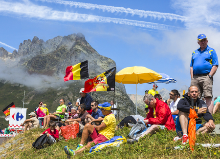 apparition: Col du Glandon, France - July 23, 2015: Image of unidentified fans  waiting for the apparition of the cyclists on Col du Glandon in Alps during the stage 18 of Le Tour de France 2015.