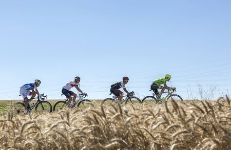 Saint-Quentin-Fallavier,France - July 16, 2016: The breakaway riding in a wheat plain during the stage 14 of Tour de France 2016.
