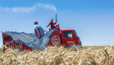 entertainment event: Saint-Quentin-Fallavier,France - July 16, 2016: Vittel vehicle during the passing of Publicity Caravan in a wheat plain in the stage 14 of Tour de France 2016.Vittel is a French bottled water brand. Editorial