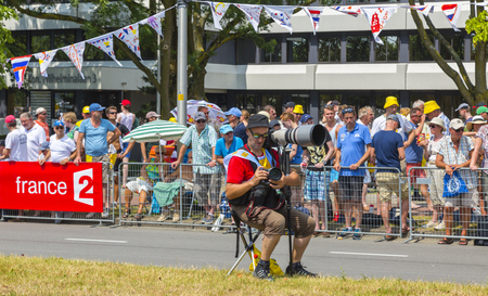 apparition: Utrecht,Netherlands - 04 July 2015: Unidentified photographer setting his tool on the roadside before the apparition of the cyclists during the first stage of Tour de France in Utrect, Netherlands on July 4, 2015.