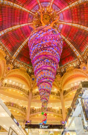 upmarket: Paris,France- December 21, 2014: Upper part of the Dior stand and the beautiful decorated Christmas decoration in Galleries Lafayette in Paris.This is a very foamous upmarket French department store opened for the first time in the center of the big city