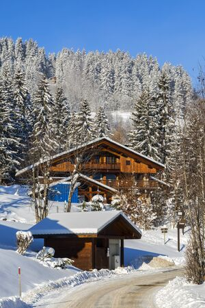 ski lodge: Image of wooden houses and a mountainous road during the winter.
