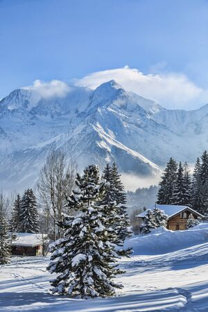 Beautirul winter landscape with wooden chalets and the top of Monta Blanc covered by windy clouds in the background. Stock Photo