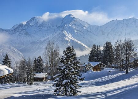BeautiFul winter landscape with wooden chalets and the top of Monta Blanc covered by windy clouds in the background.