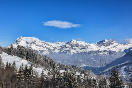 sain: Chain of peaks in Alps above the clouds and villages