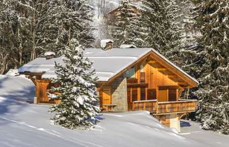 Image of a chalet located in a forest covered in snow.