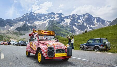 Col du Lautaret, France - July 19, 2014: Cochonou car during the passing of the advertising caravan on mountain pass Lautaret during the stage 14 of Le Tour de France 2014. Before the appearance of the cyclists there is a caravan of advertising cars of th Editorial
