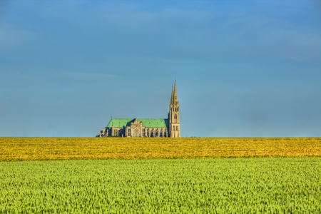 Image of the Cathedral of Our Lady of Chartres seen from outside of the city above the fields of cereals which surround the locality.This is a very famous Gothic cathedral which contains original stained glass from the 13th century. Фото со стока