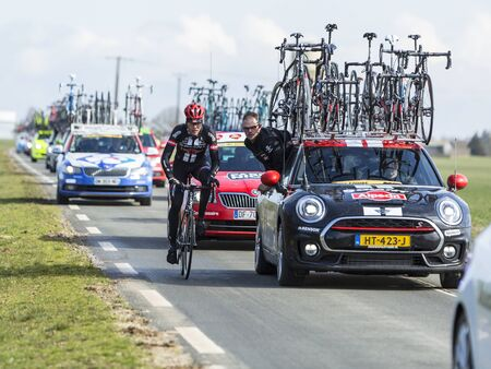 next stage: Le Gaut Saint Denis,France- March 7,2016: A cyclist of Team Giant-Alpecin discussing with a staff member while riding next to his team car in Eure et Loire region of France during the first stage of Paris-Nice 2016. Editorial