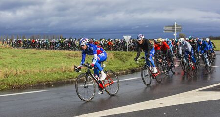 rudy: Cernay-la-Ville, France - March 5, 2017: The peloton taking a curve on a wet road during the first stage of Paris-Nice on 5 March, 2017. Editorial