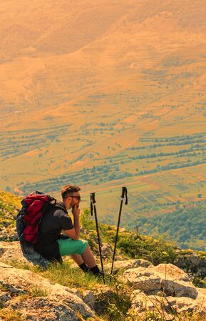 Image of a hiker resting on rocks and looking in the distance in mountains. Location: Apuseni Mountains,Transylvania,Romania. Stock Photo