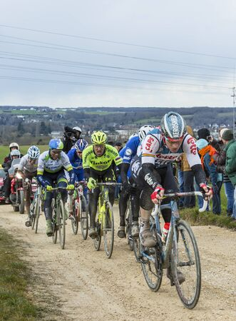 peloton: Vendome,France- March 7,2016:The cyclists rinding in the peloton on a dirty road,Tertre de la Motte, in Vendome, during the first stage of Paris-Nice 2016.