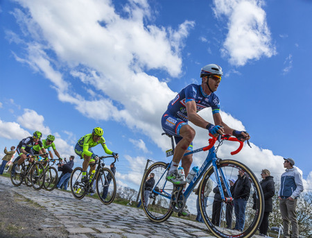 peloton: Hornaing ,France - April 10,2016: The Belgian cyclist Dimitri Claeys of Wanty? Groupe Gobert Team riding in the peloton on a paved road in Hornaing, France during Paris Roubaix on 10 April 2016.