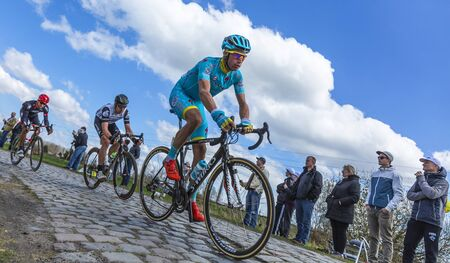 frederik: Hornaing ,France - April 10,2016: Group of three cyclists riding in the peloton on a paved road in Hornaing, France during Paris Roubaix on 10 April 2016.