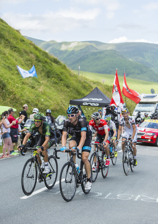 Col de Peyresourde,France- July 23, 2014: Group of cyclists, including Bernhard Eisel of Team Sky and Bryan Coquard of Team Europcar, climbing the road to Col de Peyresourde in Pyrenees Mountains during the stage 17 of Le Tour de France on 23 July 2014.