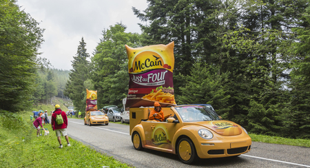 Col de Platzerwasel, France - July 14, 2014: McCain vehicles during the passing of the Publicity Caravan in front of the audience on the road to Mountain Pass Platzerwasel, in Vosges mountains, in the stage 10 of Le Tour de France on July 14 2014. Before