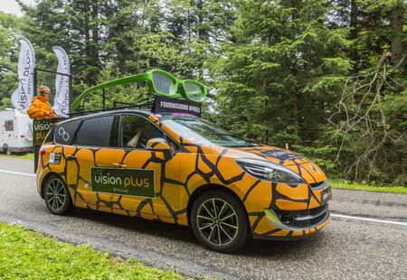 Col de Platzerwasel, France - July 14, 2014: Vision Plus vehicle during the passing of the Publicity Caravan in front of the audience on the road to Mountain Pass Platzerwasel, in Vosges mountains, in the stage 10 of Le Tour de France on July 14 2014. Vis Editorial