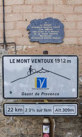 simpson: Bedoin, France - 14 July 2017: Image of the road indicator located in Bedoin and signaling the start of one of the most famous cycling road in the world: the classical ascent from Bedoin to the top of Mont Ventoux. This road is often used by the most famo Editorial