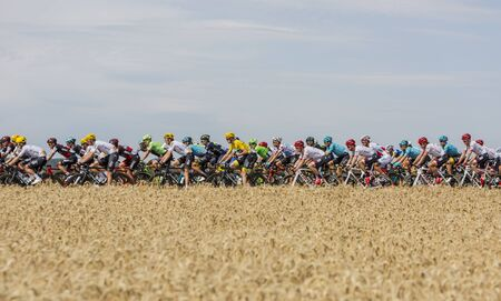 Vendeuvre-sur-Barse, France - 6 July, 2017: The peloton passes through a region of wheat fields during the stage 6 of Tour de France 2017. Yellow Jersey - Chris Froome, Polka Dot Jersey - Fabio Aru, Green Jersey - Arnaud Demare Editorial