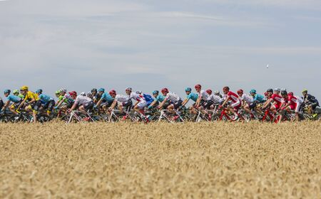 Vendeuvre-sur-Barse, France - 6 July, 2017: A cyclists water-can flies over the peloton passing through a region of wheat fields during the stage 6 of Tour de France 2017. Yellow Jersey - Chris Froome, Polka Dot Jersey - Fabio Aru, Green Jersey - Arnaud  Editorial