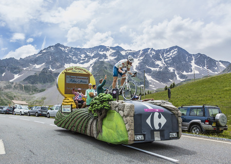 retailer: Col du Lautaret, France - July 19, 2014: The Carrefour during the passing of the advertising caravan on mountain pass Lautaret during the stage 14 of the Tour de France 2014. Before the appearance of the cyclists there is a caravan of advertising cars Of