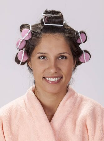 Portrait of a young smiling brunette with curlers.
