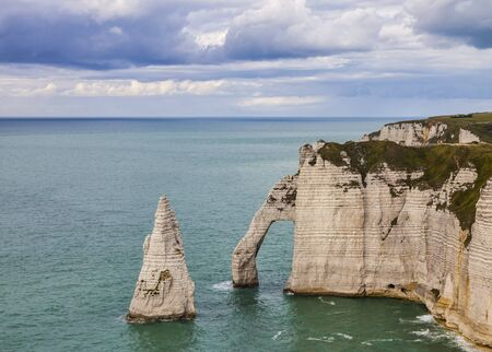 specific: Specific cliffs in Etretat in the Upper-Normandy region in Northern France at low tide: the needle rock and the stone arch.