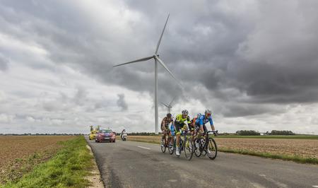 Le Gault-Saint-Denis, Frankrijk - 08 oktober 2017: Het wegrijden op een weg in de vlakte met windmolens in een bewolkte dag tijdens het Parcours-Tours-fietswedstrijden.
