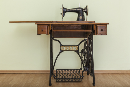 Bacau,Romania - May 16, 2011: Image of the old Singer Sewing machine in a empty room with parquet. Issac Singer built the first sewing machine with vertical needle movement powered by foot treadle.