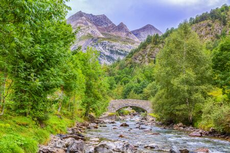 gave: Image of a stone bridge over the River Gave de Gavarnie few kilometers downstream of the Cirque de Gavarnie in Pyrenees Mountains. Stock Photo