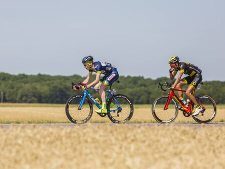 Vendeuvre-sur-Barse, France - 6 July, 2017: Two cyclists (Backaert of Wanty-Groupe Gobert Team, Quemeneur of Direct Energie Team) in the breakaway pass through a region of wheat fields during the stage 6 of Tour de France 2017.