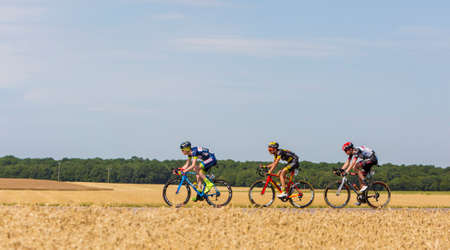 Vendeuvre-sur-Barse, France - 6 July, 2017: Three cyclists (Backaert of Wanty-Groupe Gobert Team, Quemeneur of Direct Energie Team, Laengen of UAE Team Emirates) in the breakaway pass through a region of wheat fields during the stage 6 of Tour de France 2