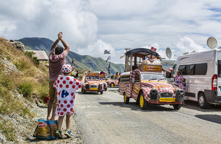 Pass of the Iron Cross, France - July 25, 2015: Kid in Polka-Dot Jersey enjoying the passing of the Publicity Caravan on the road to the Cross of Iron Cross in Alps during the stage 20 of The Tour de France 2015.