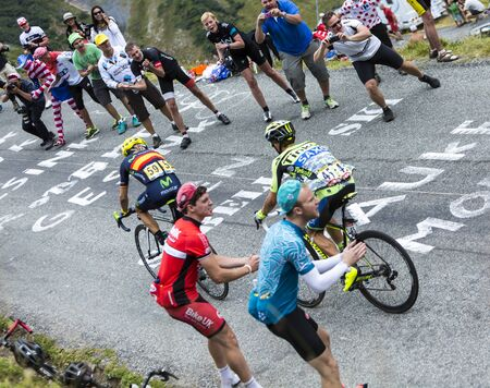 Col du Glandon, France - July 24, 2015: Excited spectators cheering two cyclists while climbing the road to Col du Glandon in Alps, during the stage 19 of Le Tour de France 2015. Selective focus on the audience.