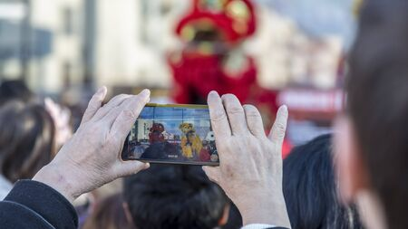 Noisy-le-Grand, France - February 18,2018: Image of the hands of a senior woman filming using a smartphone during the Chinese New Year parade in Nosy-le-Grand on February 18,2018. Editorial