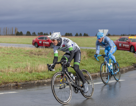 Cernay-la-Ville, France - March 5, 2017: Two cyclists, Romain Hardy and Gatis Smukulis riding on a wet road during the first stage of Paris-Nice on 5 March, 2017. Editorial