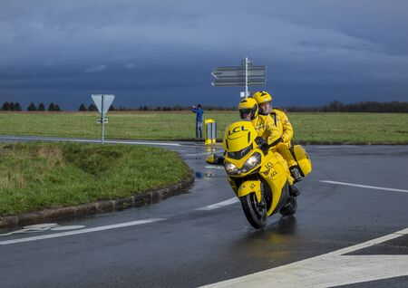 Cernay-la-Ville, France - March 5, 2017: The yellow LCL bike driving on a wet road during the first stage of Paris-Nice on 5 March, 2017.