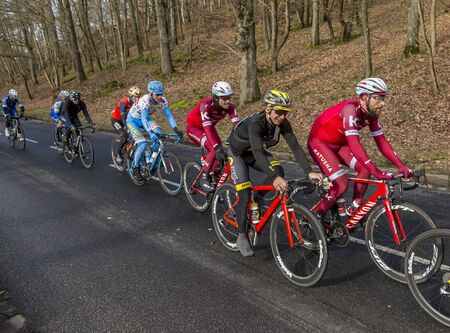 Cote de Senlisse, France - 5 March, 2017: Group of cyclists riding in the peloton on Cote de Senlisse during the first stage of Paris-nice on 05 March 2017.