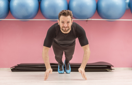 Image of a young handsome man clapping his hands while he is doing pushups in a gym. Stock Photo