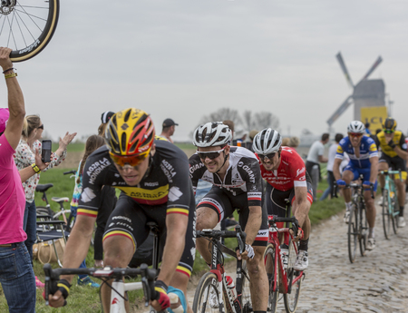 Templeuve, France - April 08, 2018: The Dutch cyclist Mike Teunissen of Team Sunweb riding in the peloton on the cobblestone road in Templeuve in front of the traditional Vertain Windmill during Paris-Roubaix 2018.