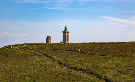 Unidentifiable people hiking close to the lighthouse from Cap de Frehel on Armor Coastline in Brittany in North of France.