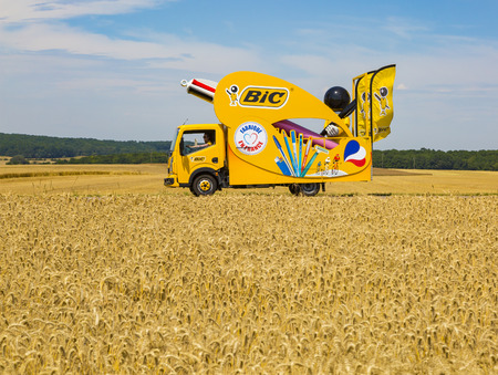 Vendeuvre-sur-Barse, France - 6 July, 2017: The fancy vehicle of BIC passes through a region of wheat fields in the Publicity Caravan before the cyclists during the stage 6 of Tour de France 2017. BIC is a global company which offers an extensive line of