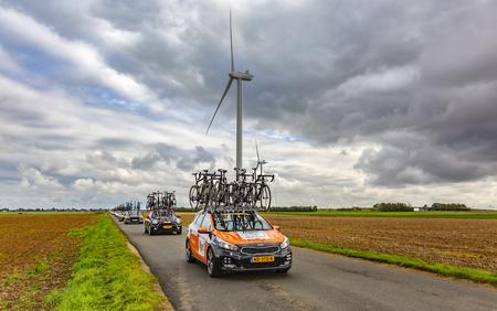 Le Gault-Saint-Denis, Frankrijk - 08 oktober 2017: Rij van technische voertuigen die rijden op een weg in de vlakte met windmolens in een bewolkte dag tijdens de wielerwedstrijd Parijs-Tours. Redactioneel