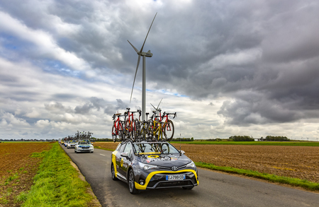 Le Gault-Saint-Denis, France - October 08, 2017: Row of technical vehicles driving on a road in the plain with windmills in a cloudy day during the Paris-Tours road-cycling race. Archivio Fotografico - 109959853